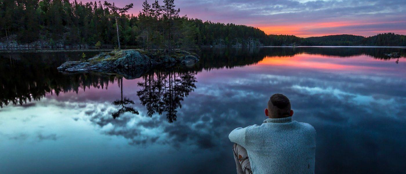 Sittende mann ved et fjellvann om kvelden